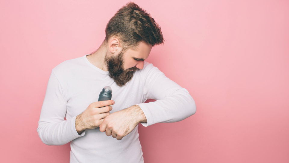 Man is looking to his armpits and smelling the smell that goes from it. Also he is holding a deodorant. Isolated on pink background