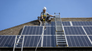 A maintenance person uses a ladder and harnesses to install equipment around a Solar panel array on the roof of a house