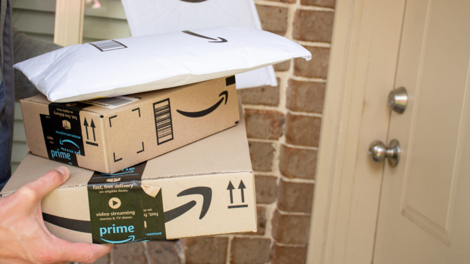 Amazon prime boxes and envelopes delivered to a front door of residential building - stock photo