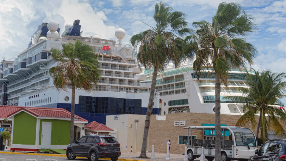 The Celebrity Millennium, left, operated by Royal Caribbean's Celebrity Cruises, docked in the Caribbean island of St. Maarten, on June 5, 2021. It sailed with about a third of the usual number of passengers, all of them vaccinated.