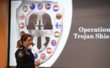 Commander Xenia Cotter, from the Australian Federal Police, walks past an Operation Trojan shield logo during a news conference, Tuesday, June 8, 2021, in San Diego. The global sting operation involved an encrypted communications platform developed by the FBI and sparked a series of raids and arrests around the world in which more than 800 suspects were arrested and more than 32 tons of drugs — cocaine, cannabis, amphetamines and methamphetamines were seized.