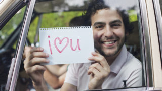 Man in car holding sign saying 'I love you' -