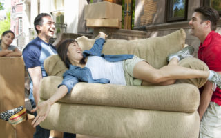 men lifting and carrying couch with woman lounging on couch, other woman leaning on moving box in the background, more moving boxes in the background, urban environment