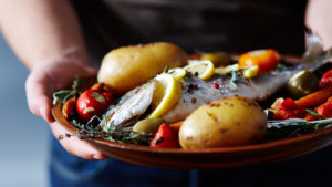 Close-up view of unrecognizable man holding plate with delicious fish baked with potatoes, vegetables, spices and lemon