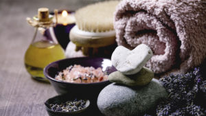 Fresh and dry lavender flowers.stones as heart shape. essential oil. pink salt. bath towel. aromatic candle on textured background.