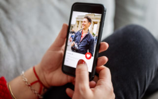 Close-up of a female using a dating app on smart phone. Woman looking at man on an online dating app on her mobile phone