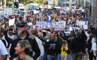 Protesters march along Broadway and George St towards Sydney Town Hall during the 'World Wide Rally For Freedom' anti-lockdown rally at Hyde Park in Sydney, Saturday, July 24, 2021.