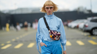 """A guest wears beige sunglasses, a pale blue with ruffled turtleneck / puffy sleeves / embroidered straps shirt, a multicolored triangular print pattern fanny pack bag, blue pants, black / white / yellow print pattern socks, after the Bianca Popp show, during """"Feeric"""" Fashion Week 2021, on July 23, 2021 in Sibiu, Romania."""