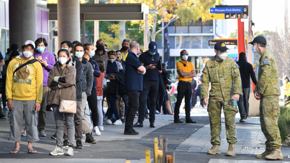 Australian Defence force members monitor a line of people waiting to receive their COVID-19 vaccine at the New South Wales health vaccination centre at Sydney Olympic Park on August 17, 2021