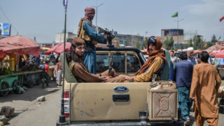 Taliban fighters on a pick-up truck move around a market area, flocked with local Afghan people at the Kote Sangi area of Kabul on August 17, 2021, after Taliban seized control of the capital following the collapse of the Afghan government.