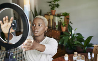 Young female influencer making adjustments to a ring light while preparing to do an online vlog post at a table at home