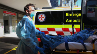 New South Wales Ambulance paramedic transports a suspected COVID-19 patient to the Emergency Department of St Vincent's Hospital